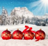 Snowy winter landscape with red and gold christmas balls