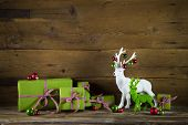 Festive wooden christmas background with presents and reindeer in red and green colors.