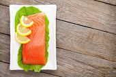 Fresh salmon fish with lemon and salad leaves on wooden table with copy space