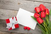 Fresh tulips, gift box and greeting card over wooden table background