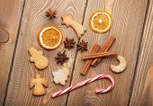 Christmas food decoration with gingerbread cookies, spices and candies. View from above on wooden background