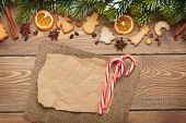 Christmas wooden background with snow fir tree, spices, gingerbread cookies and paper for copy space