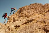 Two hikers crossing rocky terrain in the desert at sunny day