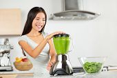 Vegetable smoothie woman blending green smoothies with blender home in kitchen. Healthy eating lifestyle concept portrait of beautiful young woman preparing drink with spinach, carrots, celery etc.
