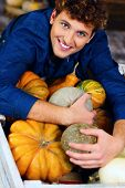Portrait of a man hugging pumpkins