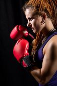 Beautiful Woman With Red Boxing Gloves, Dreadlocks On A Black Background