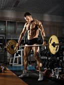 foto of execution  - very power athletic guy bodybuilder execute exercise with weight in the standing position - JPG