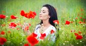 Young girl relaxing in green poppies field. Portrait of beautiful brunette woman posing in a field