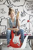 Full-length portrait of girl with electric guitar sitting on study table at home