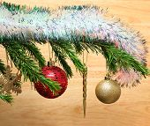 christmas holiday toys with shiny garland on fir tree twig and wood background