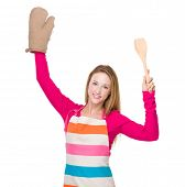 Housewife hold up with gloves and spatula