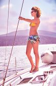 Beautiful slim female standing on the deck of yacht and enjoying beautiful sunset, active summer adventure, luxury sea cruise