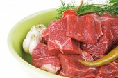 raw fresh beef meat slices in a ceramic dish with onion and red peppers isolated over white background