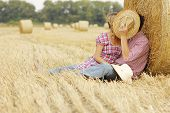 stock photo of haystack  - a in love young couple on haystacks in cowboy hats - JPG
