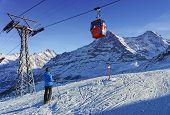 Men On Ski Near Cable Railway On Winter Sport Resort In Swiss Alps