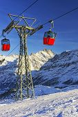 Two Red Cabins Of Cable Railway On Winter Sport Resort In Swiss Alps