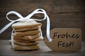 image of ginger bread  - Ginger Bread Cookies with white Ribbon and Label with the German Words Frohes Fest which means Merry Christmas - JPG