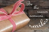 Gift With Red Ribbon Saying Be The Reason Someone Smiles