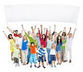 Multi-Ethnic Group Of Casual People With Children Raising Their Arms As They Hold Empty Banner For A Copy Space.