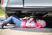 Little girl in pink waistcoat and striped hat lying under car with socket wrench in hands