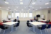 Bright meeting room with four tables and modern equipment