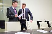 Two businessmen standing with a blank sheet of paper near conference table