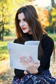 Young brunette girl studying in the park - autumn colors