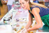 Saleswoman working at counter in groceries shop