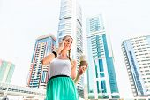Young woman telephoning with mobile phone, drinking coffee in metropolitan city Dubai