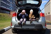 Children sitting in open trunk of car: boy with fishing rod, girl looking through binoculars