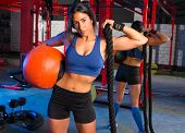 Brunette gym woman with weighted ball and rope posing