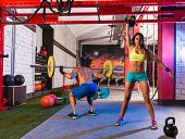 Barbell weight lifting man and woman rising kettlebell gym weightlifting