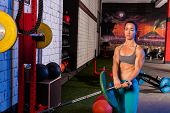 Gym girl lifting a barbell with fit strong body