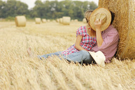 picture of haystacks  - a in love young couple on haystacks in cowboy hats - JPG
