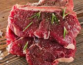 Постер, плакат: Raw T bone Steak With Seasoning And Rosemary On Wooden Board