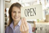 image of local shop  - Store Owner Turning Open Sign In Shop Doorway - JPG