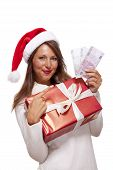 picture of vivacious  - Vivacious beautiful young woman wearing a Santa hat with a large red Christmas gift and money conceptual of successful Xmas shopping and payment on white - JPG