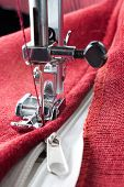 stock photo of sewing  - sewing a white zipper on a sewing machine. sewing process