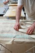 pic of fermentation  - Male baker kneading and placing pieces of bread over fermentation sheet - JPG