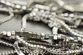 picture of chains  - Pile of assorted silver chains with shiny box chains cube chains and ordinary linked chain on a grey background conceptual of fashion jewellery  - JPG