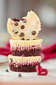 stock photo of red velvet cake  - Stack of red velvet mini cheesecakes with small heart on the side - JPG