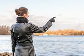 stock photo of indications  - An adult with a chignon and wearing a black leather coat stays close to the river and point her finger to indicate something interesting on the opposite bank  - JPG