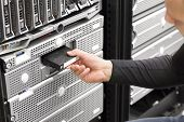 stock photo of magnetic tape  - It engineer or consultant working with backup server in racks - JPG