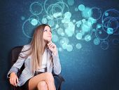 stock photo of blouse  - Woman in jacket and blouse sits on chair and looking up - JPG