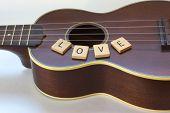 stock photo of ukulele  - An antique soprano Ukulele in still life with the word  - JPG
