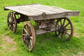 stock photo of wagon wheel  - Empty old rural wooden wagon stands on green grass - JPG
