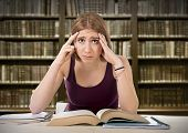 stock photo of exams  - young beautiful college student girl studying busy for university exam worried desperate and in stress feeling tired and test pressure sitting on desk with book in youth education concept - JPG