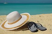 stock photo of thong  - white beach hat and thongs on sand - JPG