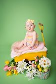 foto of baby easter  - Baby girl in Easter outfit with Easter Eggs and tulip flowers sitting in a yellow cart - JPG