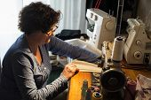 image of sewing  - Middle aged woman sewing in a sewing workshop - JPG